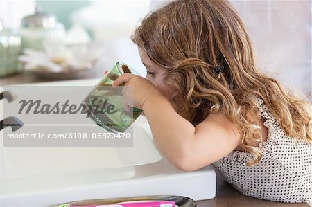 Cute little girl drinking water at bathroom sink Stock Photo - Premium Royalty-Free, Image code: 6108-05870470