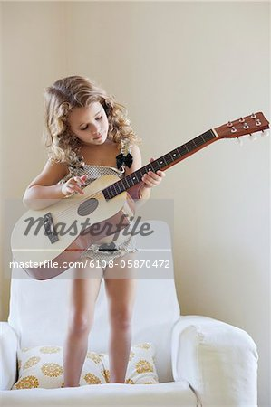 Cute little girl standing on a sofa and playing a guitar Stock Photo - Premium Royalty-Free, Image code: 6108-05870472