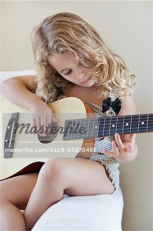 Cute little girl playing a guitar Stock Photo - Premium Royalty-Free, Image code: 6108-05870481