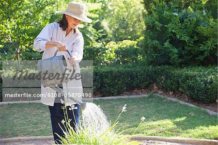 Senior woman in straw hat watering plants in a garden Stock Photo - Premium Royalty-Free, Image code: 6108-05870490