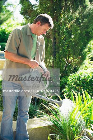 Mature man watering plants in a garden Stock Photo - Premium Royalty-Free, Image code: 6108-05870495