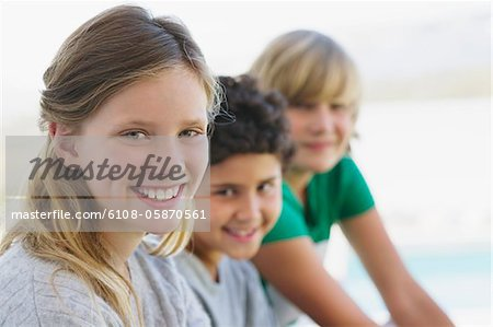 Portrait of a girl smiling with her two brothers Stock Photo - Premium Royalty-Free, Image code: 6108-05870561