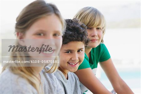 Portrait of a girl smiling with her two brothers Stock Photo - Premium Royalty-Free, Image code: 6108-05870581