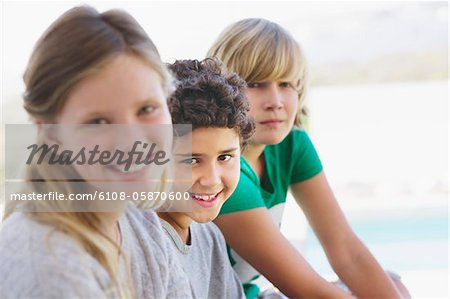 Portrait of a girl smiling with her two brothers Stock Photo - Premium Royalty-Free, Image code: 6108-05870600
