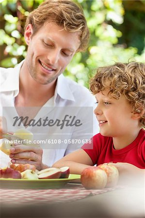 Father peeling apple with son Stock Photo - Premium Royalty-Free, Image code: 6108-05870638