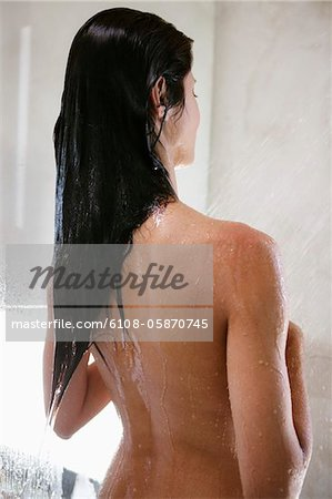 Rear view of woman taking a shower Stock Photo - Premium Royalty-Free, Image code: 6108-05870745