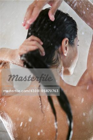 Rear view of woman taking a shower Stock Photo - Premium Royalty-Free, Image code: 6108-05870763