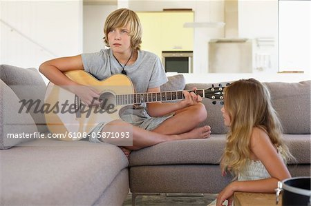 Girl looking at a her brother playing a guitar Stock Photo - Premium Royalty-Free, Image code: 6108-05871093