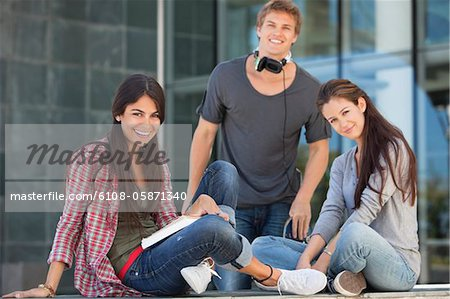 Smiling young students sitting in campus Stock Photo - Premium Royalty-Free, Image code: 6108-05871340