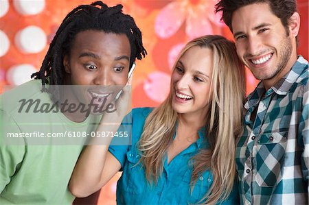 Friends talking on a mobile phone in a bar Stock Photo - Premium Royalty-Free, Image code: 6108-05871455