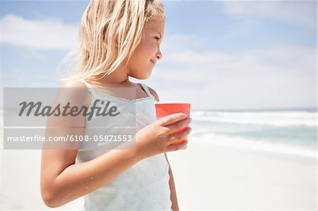 Girl holding a disposable glass on the beach Stock Photo - Premium Royalty-Free, Image code: 6108-05871553