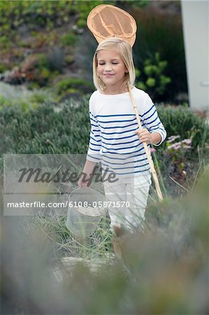 Girl carrying net and bucket for fishing Stock Photo - Premium Royalty-Free, Image code: 6108-05871570