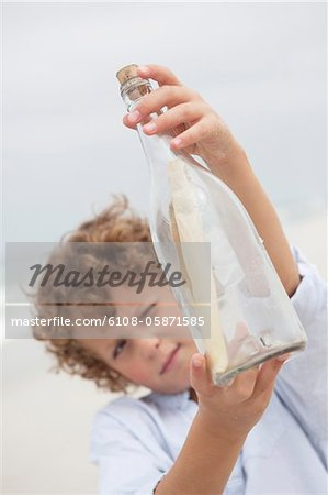 Boy looking at message in a bottle on beach Stock Photo - Premium Royalty-Free, Image code: 6108-05871585