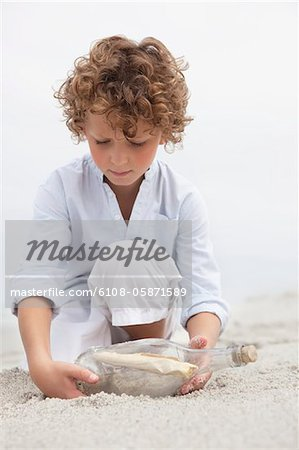 Cute boy looking at message in a bottle on beach Stock Photo - Premium Royalty-Free, Image code: 6108-05871589