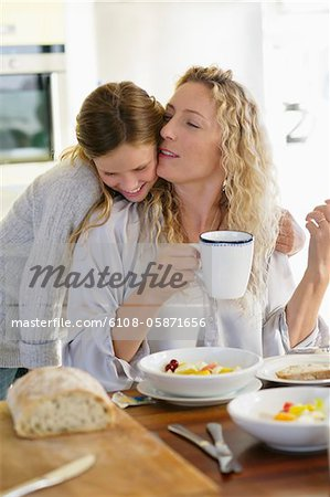 Mid adult woman kissing her daughter at a dining table Stock Photo - Premium Royalty-Free, Image code: 6108-05871656