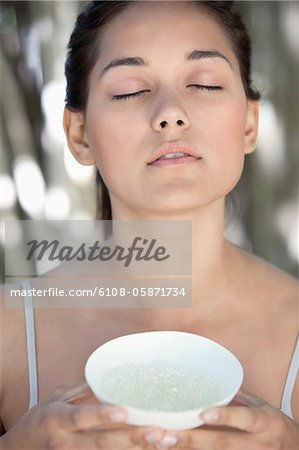 Beautiful young woman holding a bowl with bath salt Stock Photo - Premium Royalty-Free, Image code: 6108-05871734