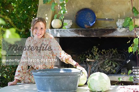 Portrait of a little girl with cabbage on table outdoors Stock Photo - Premium Royalty-Free, Image code: 6108-05871774