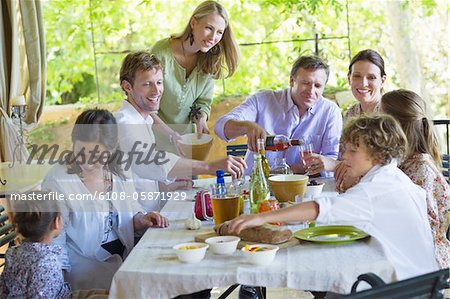 Multi generation family eating food at house Stock Photo - Premium Royalty-Free, Image code: 6108-05871929