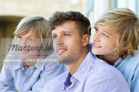 Smiling man and children looking away together Stock Photo - Premium Royalty-Free, Image code: 6108-05872040