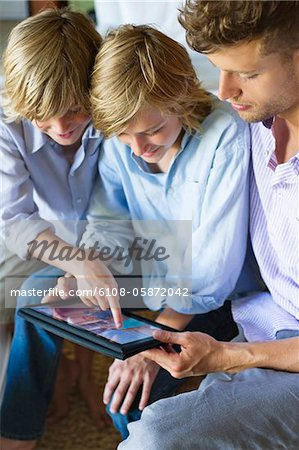 Man and two little boy looking at digital tablet Stock Photo - Premium Royalty-Free, Image code: 6108-05872042