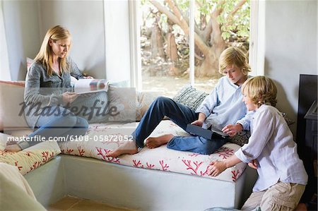 Children using digital tablet while mother reading magazine at house Stock Photo - Premium Royalty-Free, Image code: 6108-05872052