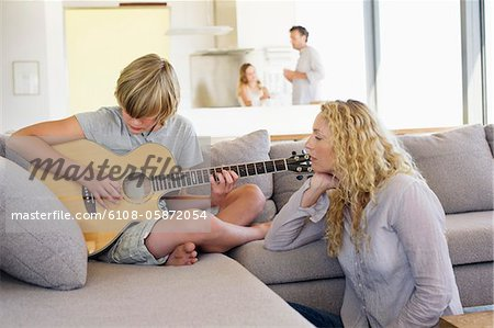 Teenage boy playing a guitar and his mother listening Stock Photo - Premium Royalty-Free, Image code: 6108-05872054