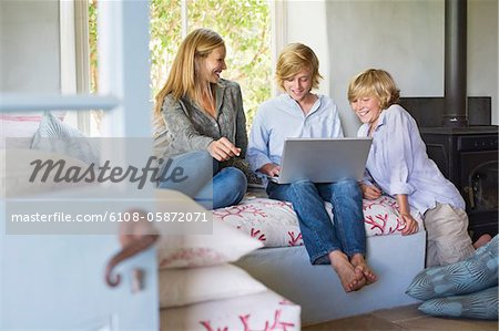 Children and their mother using laptop at house Stock Photo - Premium Royalty-Free, Image code: 6108-05872071