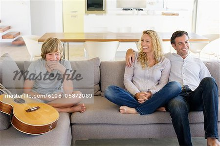 Family sitting on a couch and smiling Stock Photo - Premium Royalty-Free, Image code: 6108-05872089