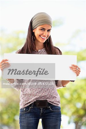 Portrait of a woman holding a blank placard Stock Photo - Premium Royalty-Free, Image code: 6108-05872135