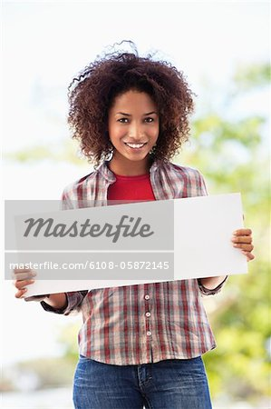 Portrait of a woman holding a blank placard Stock Photo - Premium Royalty-Free, Image code: 6108-05872145
