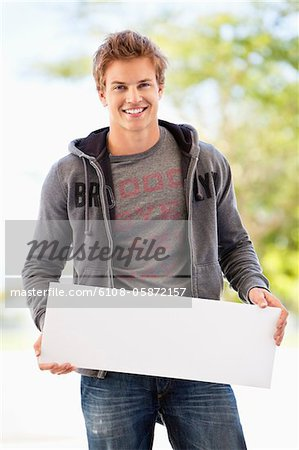 Portrait of a man holding a blank placard Stock Photo - Premium Royalty-Free, Image code: 6108-05872157