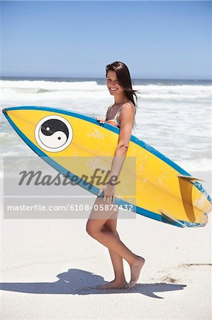 Woman walking on the beach with surfboard Stock Photo - Premium Royalty-Free, Image code: 6108-05872432