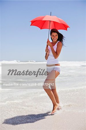 Woman walking on the beach with an umbrella Stock Photo - Premium Royalty-Free, Image code: 6108-05872492