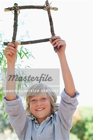 Portrait of a cute little boy holding frame of driftwood with arms raised outdoors Stock Photo - Premium Royalty-Free, Image code: 6108-05872663