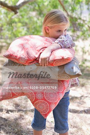 Little girl carrying pillows outdoors Stock Photo - Premium Royalty-Free, Image code: 6108-05872709
