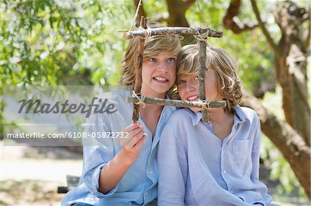 Portrait of children looking through frame of driftwood outdoors Stock Photo - Premium Royalty-Free, Image code: 6108-05872732