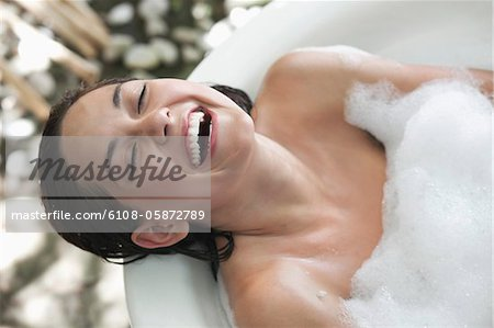 Beautiful young woman taking bubble bath and smiling Stock Photo - Premium Royalty-Free, Image code: 6108-05872789