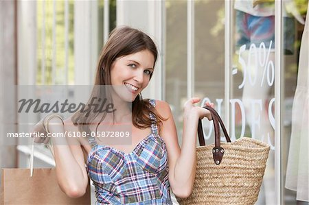 Woman holding shopping bag and smiling, Paris, Ile-de-France, France Stock Photo - Premium Royalty-Free, Image code: 6108-05872809