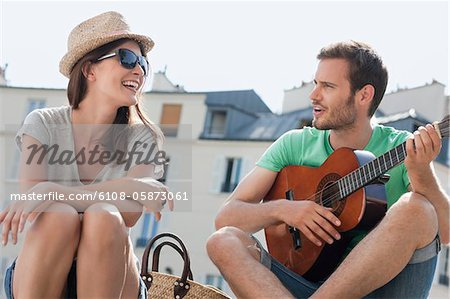 Man playing a guitar with a woman smiling, Canal St Martin, Paris, Ile-de-France, France Stock Photo - Premium Royalty-Free, Image code: 6108-05873061