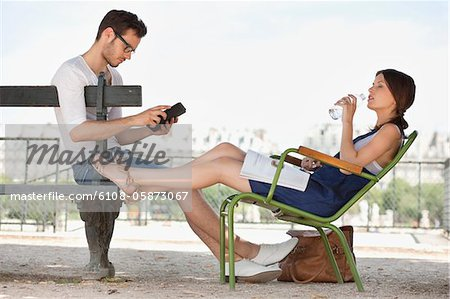Woman drinking water and her husband using a digital tablet, Jardin des Tuileries, Paris, Ile-de-France, France Stock Photo - Premium Royalty-Free, Image code: 6108-05873067