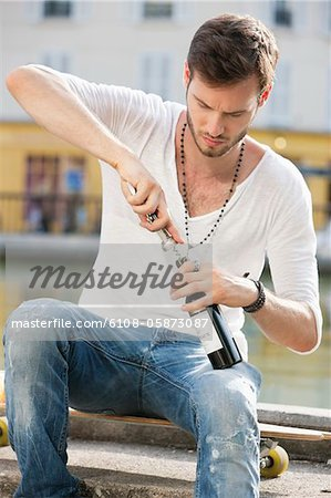 Man opening a wine bottle with a corkscrew, Paris, Ile-de-France, France Stock Photo - Premium Royalty-Free, Image code: 6108-05873087
