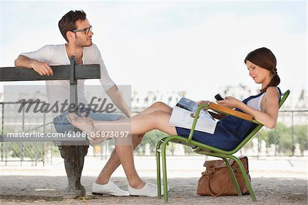 Woman using a mobile phone with a man sitting in front of her, Jardin des Tuileries, Paris, Ile-de-France, France Stock Photo - Premium Royalty-Free, Image code: 6108-05873097