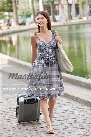 Woman pulling a suitcase and smiling, Paris, Ile-de-France, France Stock Photo - Premium Royalty-Free, Image code: 6108-05873205