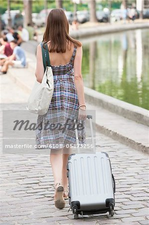 Rear view of a woman pulling a suitcase, Paris, Ile-de-France, France Stock Photo - Premium Royalty-Free, Image code: 6108-05873256