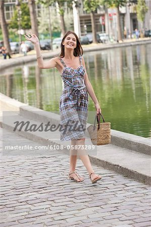 Woman waving her hand and smiling, Paris, Ile-de-France, France Stock Photo - Premium Royalty-Free, Image code: 6108-05873289