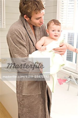 Young man in bathrobe with baby in bathroom Stock Photo - Premium Royalty-Free, Image code: 6108-05873392