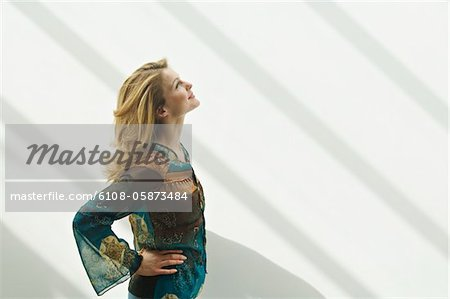 Young woman in profile looking up, arms akimbo Stock Photo - Premium Royalty-Free, Image code: 6108-05873484