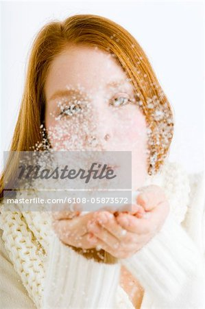 Close-up of a young woman blowing snow from her cupped hands Stock Photo - Premium Royalty-Free, Image code: 6108-05873572