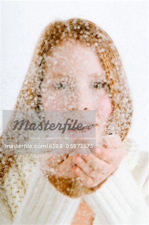 Portrait of a young woman blowing snow from her cupped hands Stock Photo - Premium Royalty-Free, Image code: 6108-05873573