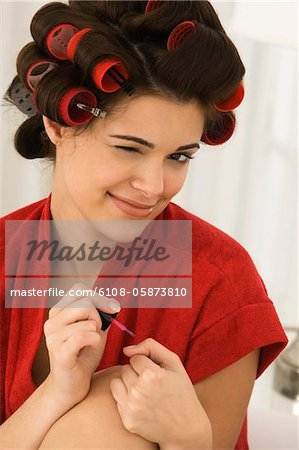 Close-up of a woman painting finger nails Stock Photo - Premium Royalty-Free, Image code: 6108-05873810